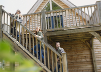 Friends climbing staircase outside wooden cabin