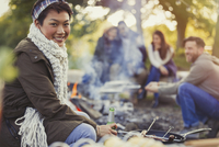 Portrait smiling woman drinking beer with friends at campfire 11086029518| 写真素材・ストックフォト・画像・イラスト素材|アマナイメージズ
