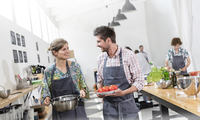 Couple carrying food in cooking class kitchen