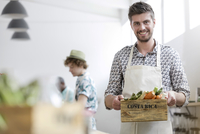 Portrait smiling man holding fresh vegetables in cooking class kitchen