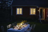 Candlelight garden party dinner outside illuminated house at night
