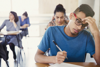 Serious male college student taking test at desk in classroom