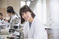 Portrait confident female college student using microscope in science laboratory classroom