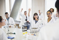 College students raising hands in science laboratory classroom