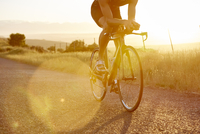Male cyclist riding bike on sunny sunrise rural road