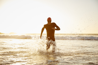 Male triathlete running out of ocean