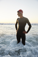 Male triathlete in wet suit standing in ocean surf