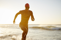 Male triathlete swimmer in wet suit running from ocean