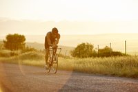 Male triathlete cyclist cycling on sunny rural road at sunrise