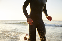 Male triathlete swimmer in wet suit running out of ocean surf
