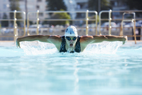 Male swimmer athlete doing butterfly stroke swimming in swimming pool