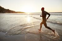 Male triathlete swimmer in wet suit running into ocean surf at sunrise 11086029869  写真素材・ストックフォト・画像・イラスト素材 アマナイメージズ
