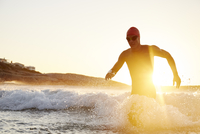 Male triathlete swimmer in wet suit running out of sunny ocean