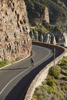 Male triathlete cyclist cycling uphill along sunny cliffs