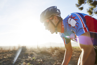 Male triathlete cyclist cycling at sunrise