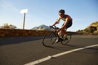Male cyclist cycling on sunny corner