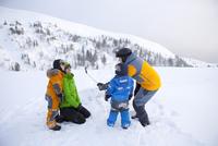 Family using selfie stick on snowy mountain 11086029890| 写真素材・ストックフォト・画像・イラスト素材|アマナイメージズ