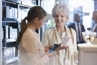 Woman buying perfume in shop from clerk with wireless credit card reader