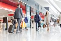 Travelers walking in airport concourse 11086029897| 写真素材・ストックフォト・画像・イラスト素材|アマナイメージズ