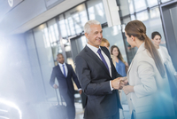 Business people greeting shaking hands in airport