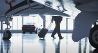 Businessman pulling suitcase outside corporate jet 11086029967| 写真素材・ストックフォト・画像・イラスト素材|アマナイメージズ