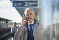 Businessman talking on cell phone outside airport