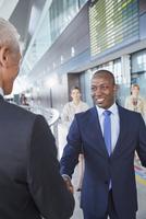 Businessmen handshaking in airport concourse