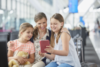 Mother and daughters using digital tablet in airport departure area 11086030043| 写真素材・ストックフォト・画像・イラスト素材|アマナイメージズ