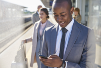 Businessman texting with cell phone on train station platform