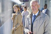 Portrait smiling businessman on sunny train station platform 11086030087| 写真素材・ストックフォト・画像・イラスト素材|アマナイメージズ