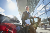 Businessman arriving at airport getting out of town car 11086030096| 写真素材・ストックフォト・画像・イラスト素材|アマナイメージズ