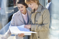 Businesswomen reading paperwork on sunny train station platform