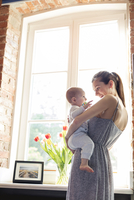 Mother holding baby daughter at window