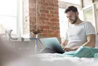 Man using laptop on bed in apartment