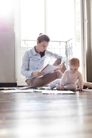 Baby daughter playing on floor near working mother