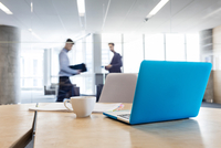 Laptop and coffee cup on conference room table with businessmen walking in background