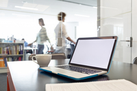 Laptop and coffee cup on desk with business people walking in background