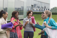 Women friends with yoga mats and coffee talking outside gym 11086031478| 写真素材・ストックフォト・画像・イラスト素材|アマナイメージズ