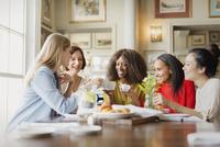 Smiling women drinking coffee and talking at restaurant table 11086031481| 写真素材・ストックフォト・画像・イラスト素材|アマナイメージズ