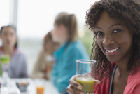 Portrait smiling woman drinking healthy green smoothie at cafe with friends
