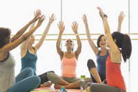 Smiling women cheering with arms raised in exercise class gym studio