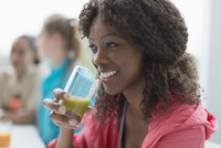 Smiling woman drinking healthy green smoothie in cafe post workout