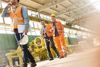 Steel workers walking and talking on coffee break in factory