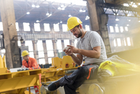 Steel worker texting with cell phone taking a break in factory
