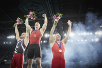 Male gymnasts celebrating victory cheering on winners podium