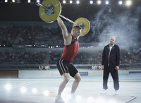 Coach watching male weightlifter squatting barbell overhead in arena 11086031781| 写真素材・ストックフォト・画像・イラスト素材|アマナイメージズ