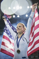 Smiling female gymnast celebrating victory holding American flag