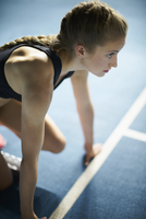 Serious focused female runner ready at starting block on sports track