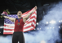 Male gymnast celebrating victory holding American flag on winners podium