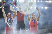 Enthusiastic male gymnasts celebrating victory on winners podium